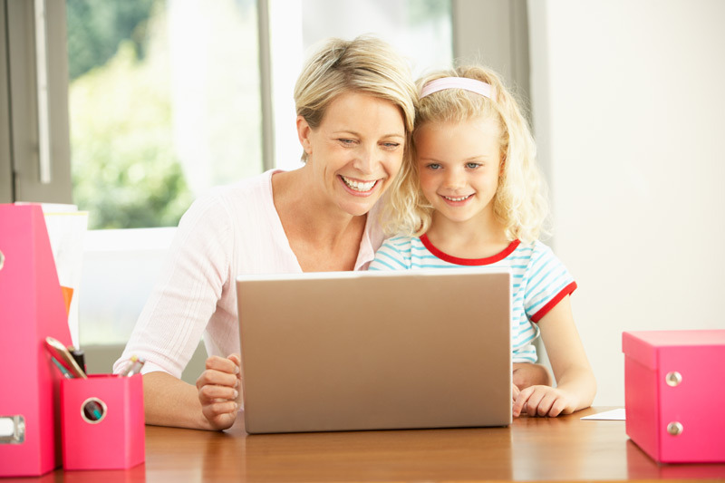 mom on laptop with young girl child